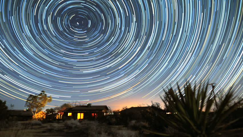 Amazing circle star trails time-lapse galaxy night sky over cabin as sun rises in Joshua Tree desert in California.