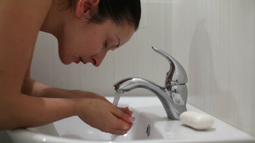 woman wash face, young female in bathroom washing with clear water