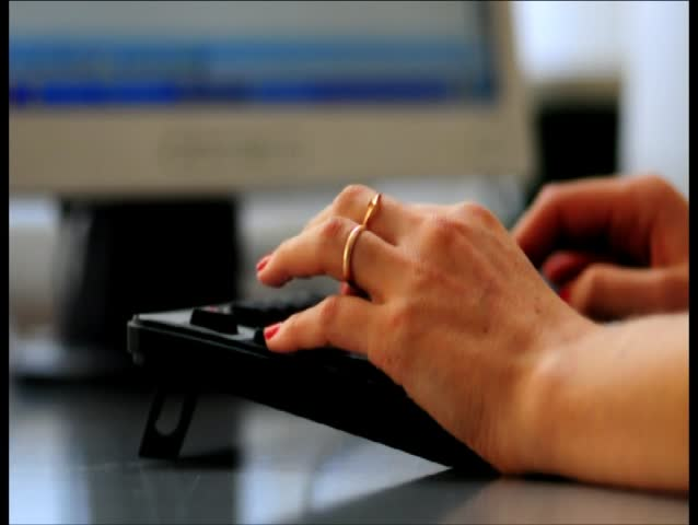 Women hands typing on a keyboard on a desk personal computer