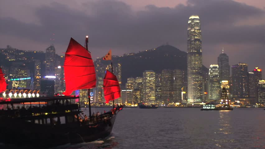 Junk ship and cruiseship in front of Hong Kong skyline at night | Shutterstock HD Video #5611571