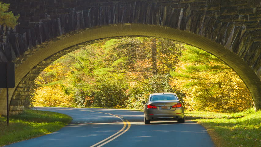 A Passenger Vehicle Driving Under a Stone Bridge on the Blue Parkway near Grandfather Mountains in Western North Carolina in the Fall with Autumn Colored Leaves on a Sunny Day.