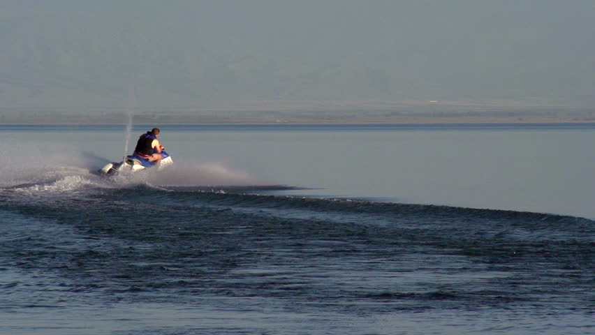 Extreme Activities. The man rolls the small son on a jet ski.  Motion at a rate of 240 fps