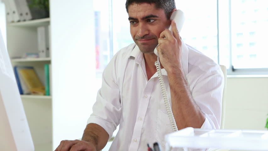 Businessman working and talking on the phone in his office