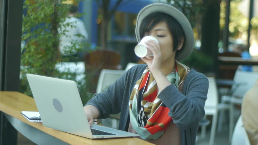Woman Enjoying Her Coffee And Laptop At A Sidewalk Cafe