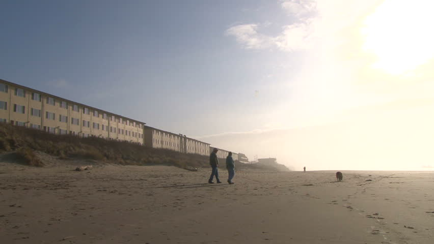 Couple with dog walk along beach where man flies kite by oceanfront hotels.