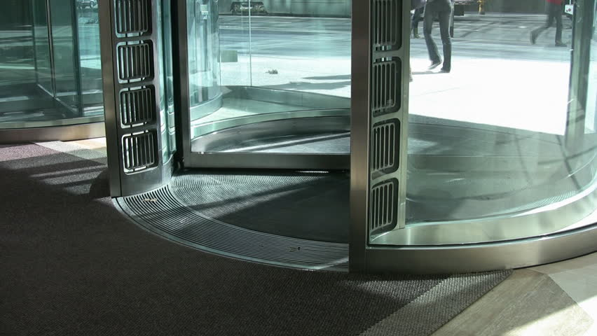 Revolving glass door at the entrance of a downtown office tower.