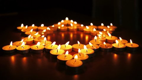 Circular, shallow depth of field, dolly shot of many candles arranged into the Jewish religious symbol the Star of David.