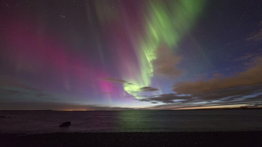 Colorful aurora (northern lights) display over the ocean at sunset. Reykjavik, Iceland