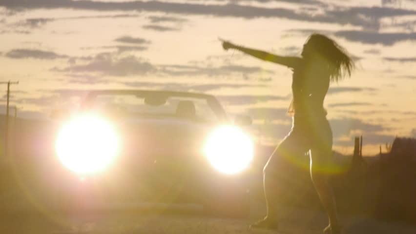 Teen Girl Dances In Car Headlights At Sunset In The Desert