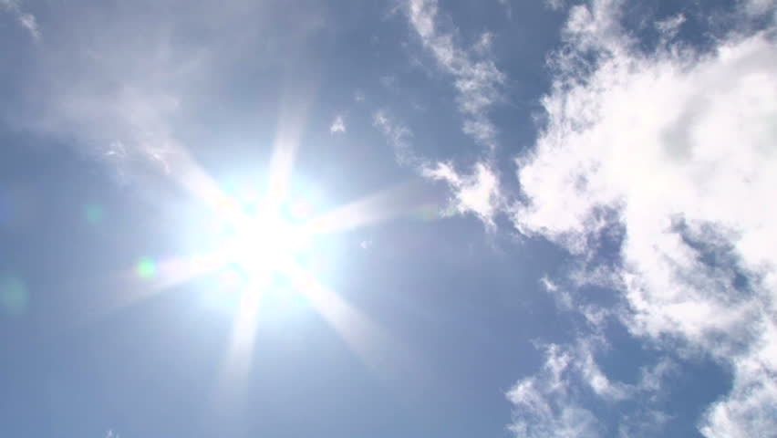 Blue sky day with bright sun shining bright with cloud over taking sun, time lapse.