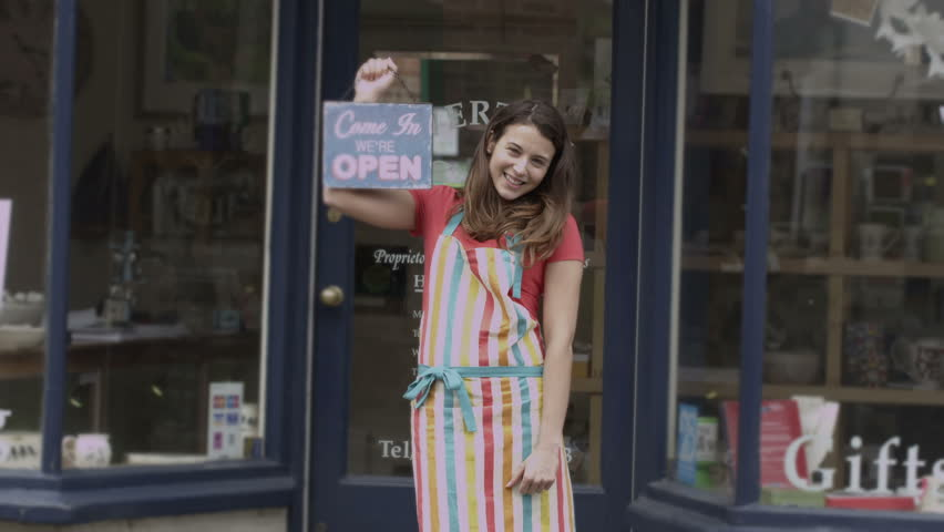 Happy female shopkeeper holds up a sign to show she is open for business | Shutterstock HD Video #5785283