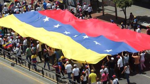 CARACAS, Venezuela - circa 201:  Protest for freedom in Venezuela.  large crowd carries a flag.