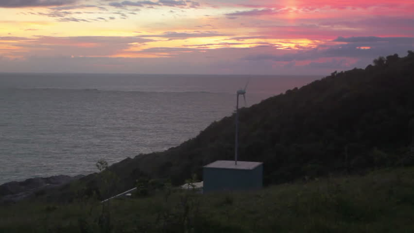 Home in Garopaba, Brazil with wind turbine providing electricity against a beautiful sunrise with sea.