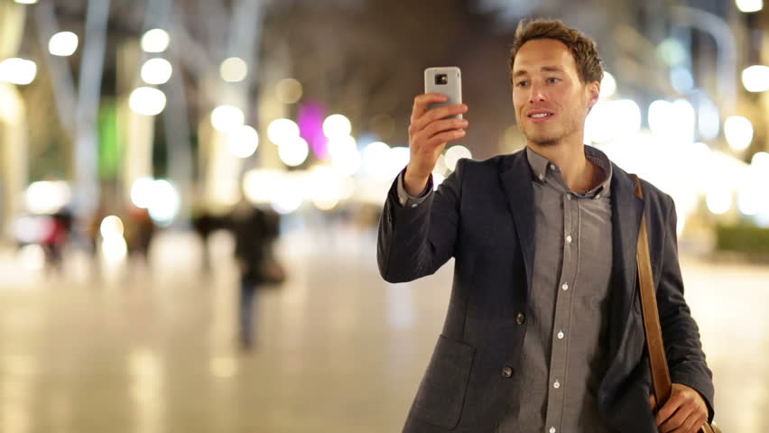 Man taking photo with camera phone at night on La Rambla, Barcelona, Spain. Young casual man taking picture with camera phone outside. | Shutterstock HD Video #5815808