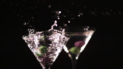 Colorful green and black olives on a cocktail stick are dropped in slow motion into a glass of martini, causing the drink to splash and spill. On a black background.