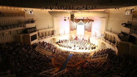 Above view of orchestra and many spectators in large concert hall