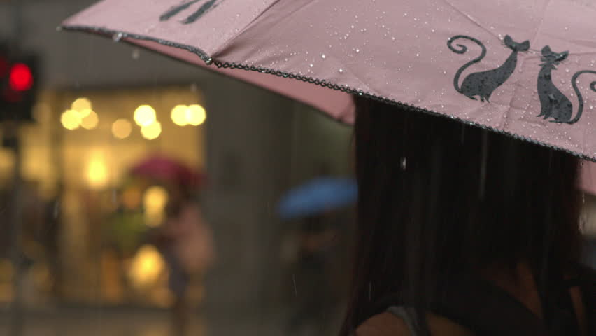 HONG KONG, CHINA - August 25, 2013 - Close-up shot in slow motion of a girl with an umbrella standing underneath rain