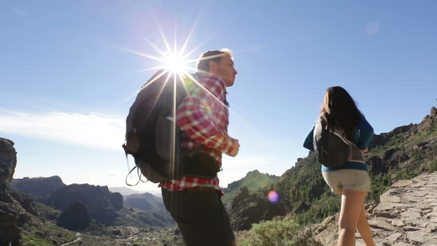 Hiking couple walking on trail. Healthy lifestyle hiker people walking in mountains. Young woman and man hikers on path to Roque Nublo, Gran Canaria, Canary Islands, Spain. | Shutterstock HD Video #5837192