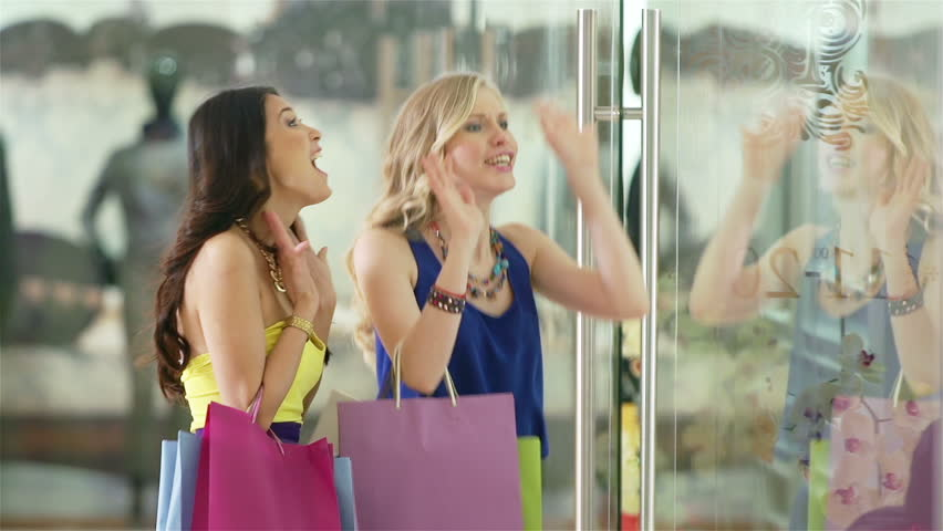 Charming girls discussing new gorgeous collection by the shopping window and then going to the clothing department to see it | Shutterstock HD Video #5853164