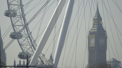 LONDON, UK - CIRCA MARCH 2014: Time Lapse of Big Ben (Elizabeth Tower, Clock Tower) through the spokes of the London Eye. Tourists can be seen in passenger capsules enjoying the views of the capital