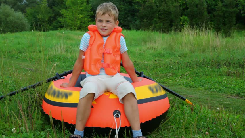 Boy dressed in life jacket dragging inflatable rubber  | Shutterstock HD Video #586168