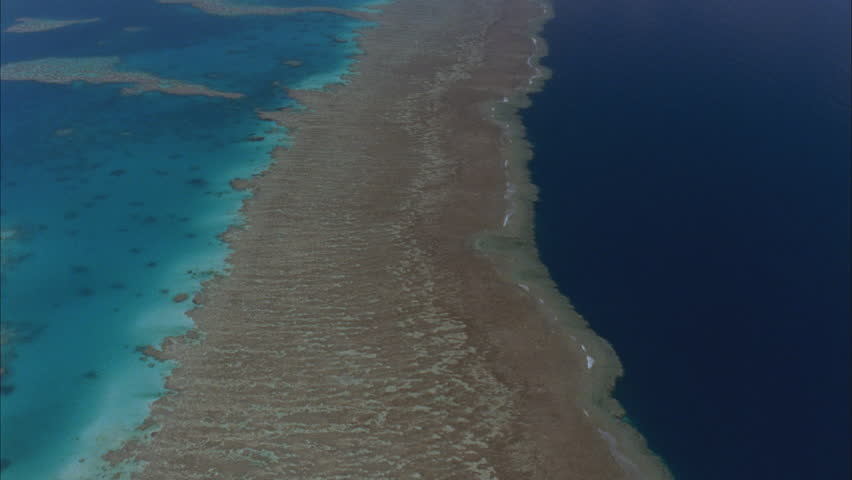 tracking shots over the great barrier reef showing reef waters one side pale blue and deep blue of outer ocean on other then isolated coral cays