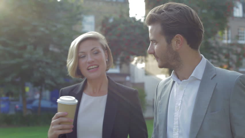 Young business couple walk through park together holding takeaway coffee cups.Shot on Canon 5D MkII at a frame rate of 25fps