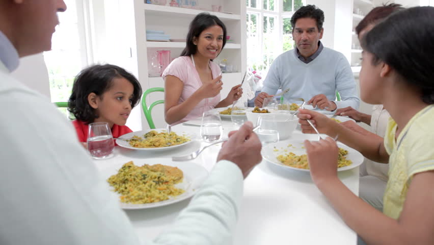 Extended Asian Indian Family Sitting Around Table At Home Eating Meal TogetherShot On Canon