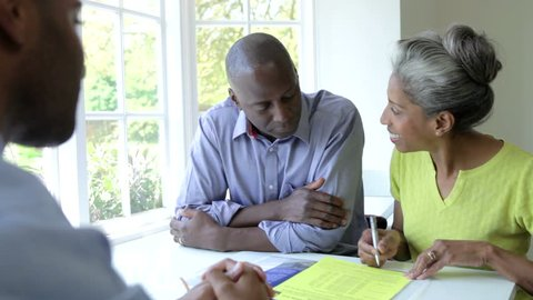 Black middle aged couple discussing document with financial advisor before signing and shaking hands.Shot on Canon 5d Mk2 with a frame rate of 25fps