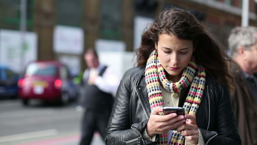 Attractive young woman using a smart phone and looking around whilst out on a public street | Shutterstock HD Video #5890157