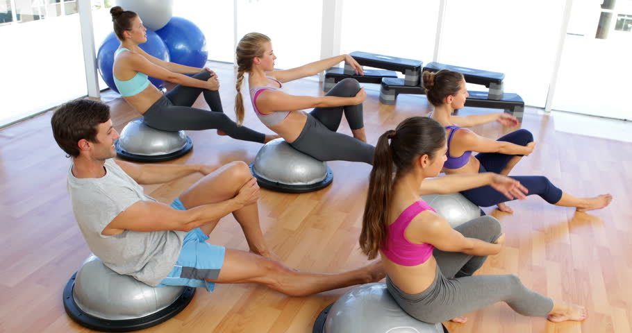 Fitness class lying on bosu balls together at the gym