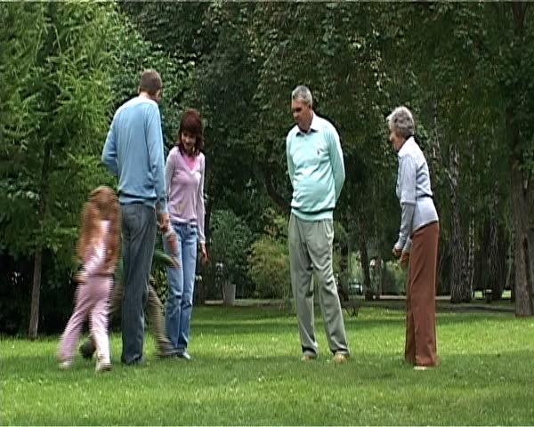 Children running near their parents and grandparents while spending time outdoors together