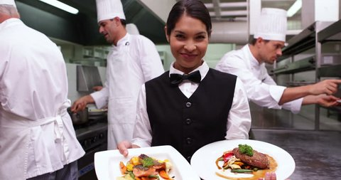 Smiling waitress showing two dishes to camera in a commercial kitchen