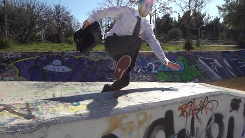 Businessman Doing Parkour. Jumping over a graffiti wall. Acrobatic getaway in slow motion.