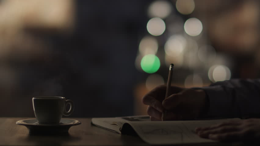 Man Drawing in notebook and Drinking Coffee in Cafe, Shot on RED Digital Cinema Camera in 4K (ultra-high definition (UHD)), so you can easily crop, rotate and zoom, without losing quality. ProResHQ