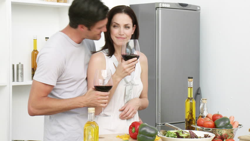 Happy couple drinking wine and eating salad in the kitchen at home. Footage in high definition