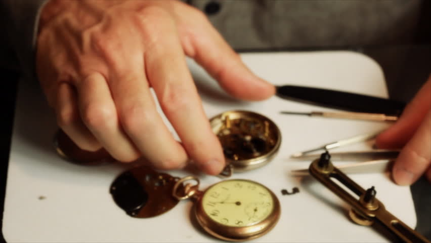 A man wearing jeweler's glasses, picks up an old pocket watch and examines the inside mechanisms.