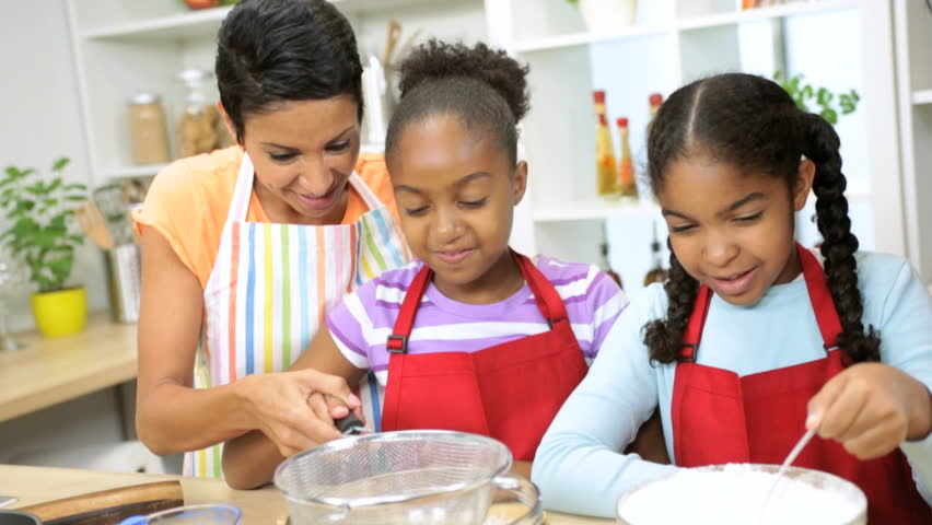 Young African American mother spending time home kitchen teaching her daughters cake baking - Ethnic Mom Cake Baking Young Daughters