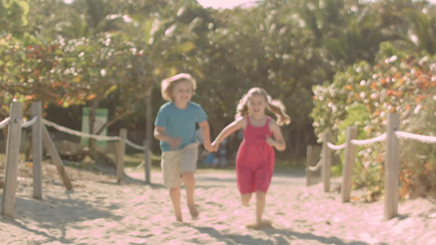 A Little Girl And Boy Hold Hands And Run Down Scenic Beach Path