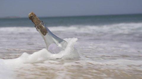 SLOW MOTION: Stranded bottle on the beach