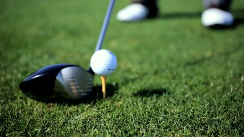 Caucasian professional golfer taking swing hitting golf ball off tee on golf course close up feet only - Professional Golfer Playing Golf Course