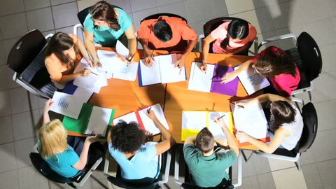 Class multi ethnic teenagers on IT business degree course working with female Caucasian tutor overhead view - Multi Ethnic Teenage Students College Classroom Overhead