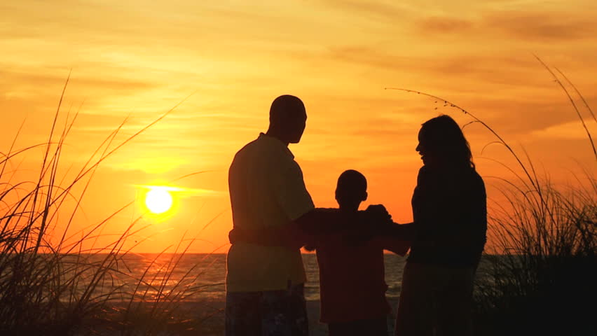 silhouette loving family arms around each other enjoying sunset together on sand dunes beach vacation