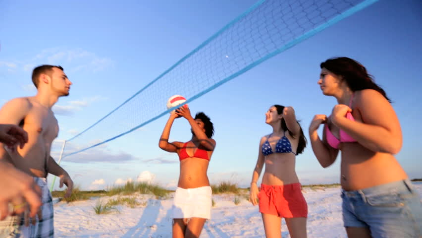 Young multi ethnic people enjoying time together playing beach volleyball weekend break slow motion shot on RED EPIC - Teenagers Enjoying Game Beach Volleyball