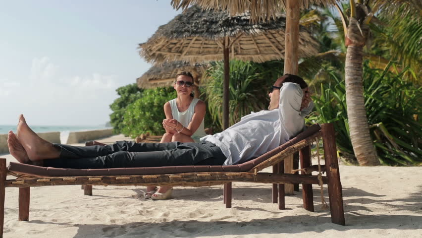 Business couple on vacations talking and relaxing on sunbeds