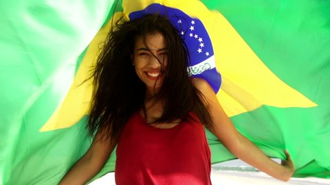 Brazilian girl with flag at the beach in slow motion