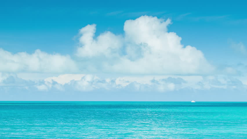 Little White Boat on Vast Tropical Ocean Waters in Bermuda with a Blue Sky Full of White Clouds on a Sunny Day.