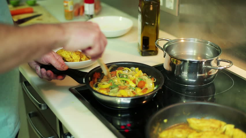 man mixing vegetables and pieces of chicken in a frying pan