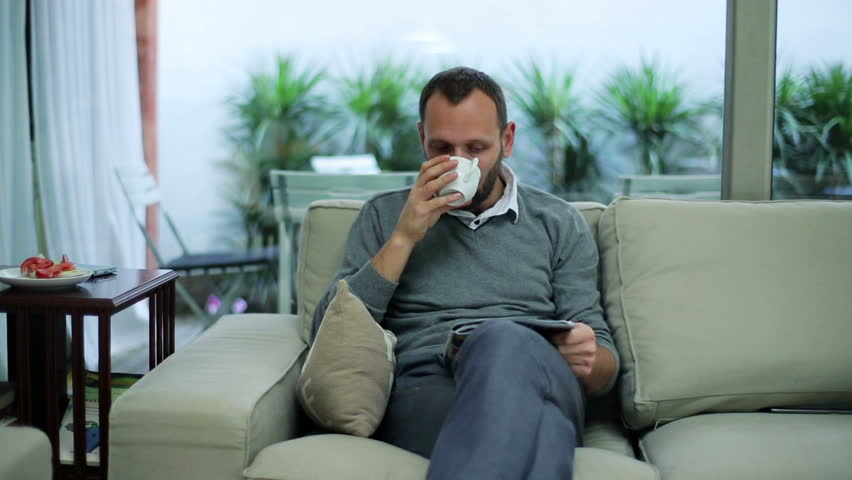 man sitting on the sofa with a newspaper and eating a sandwich