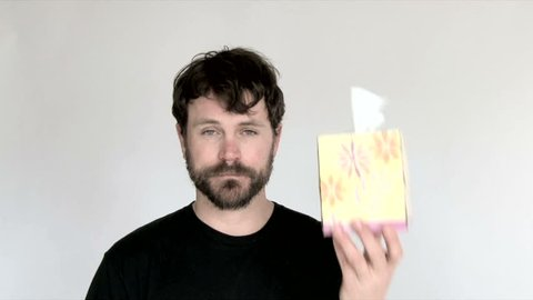 Model released man in studio sneezes and wipes nose in tissue.